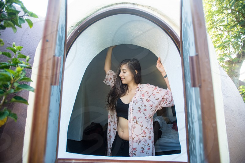 Young woman seen through a window waking up  photo