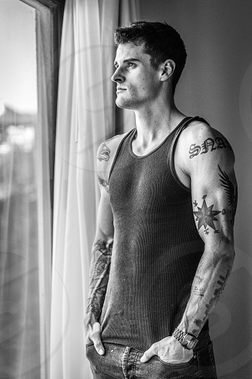 gray scale photo of man wearing black tank top with lots of tattoo on his arms standing near the window photo