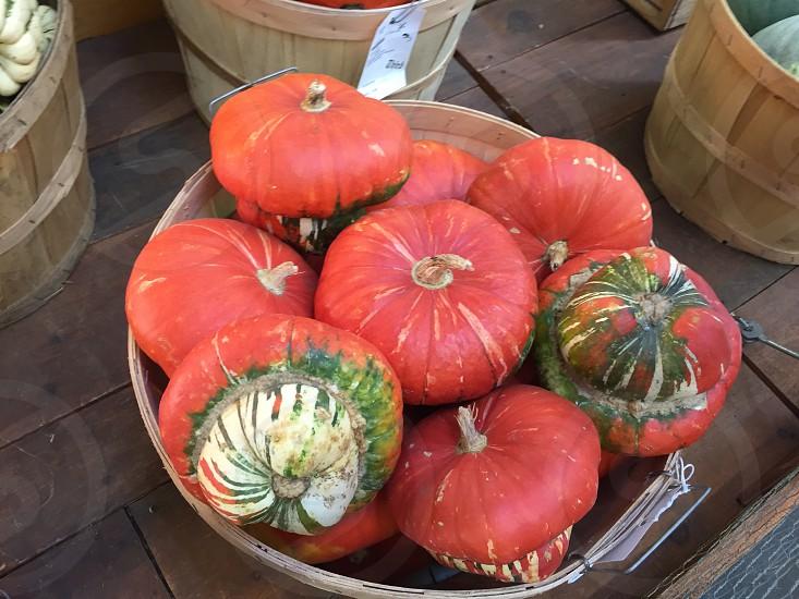 red pumpkins on brown wooden bucket photo