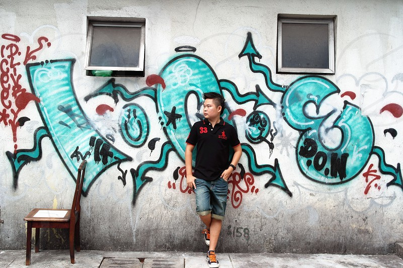 man in black polo shirt leaning on wall with graffiti photo