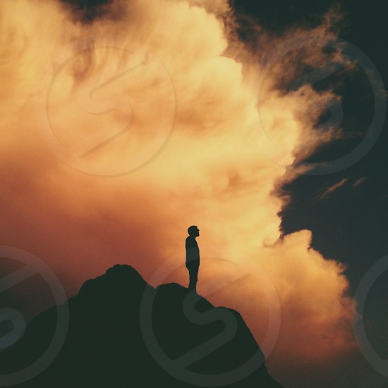 Man standing in cliff silhouette photo