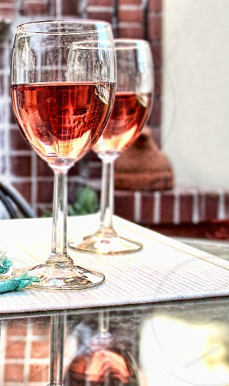 Pair of wine glasses with rose wine outdoors on a brick patio photo