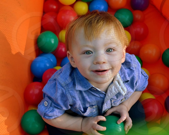 child with red hair playing in ball pit holding green ball photo