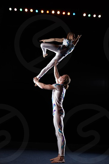 Circus artists perform different tricks. Man holding woman. photo