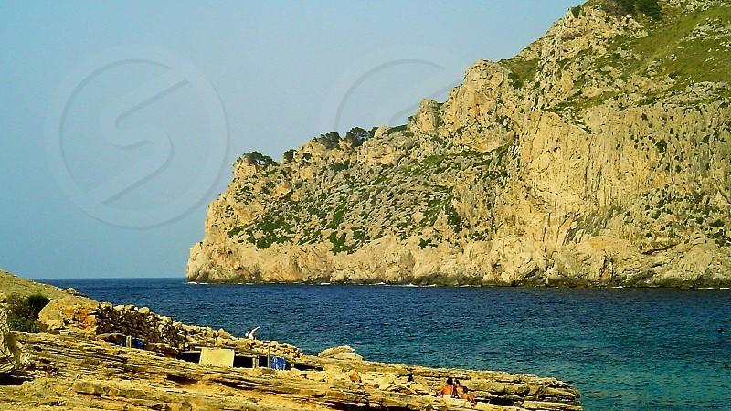 rock hill on sea side under clear sky photo