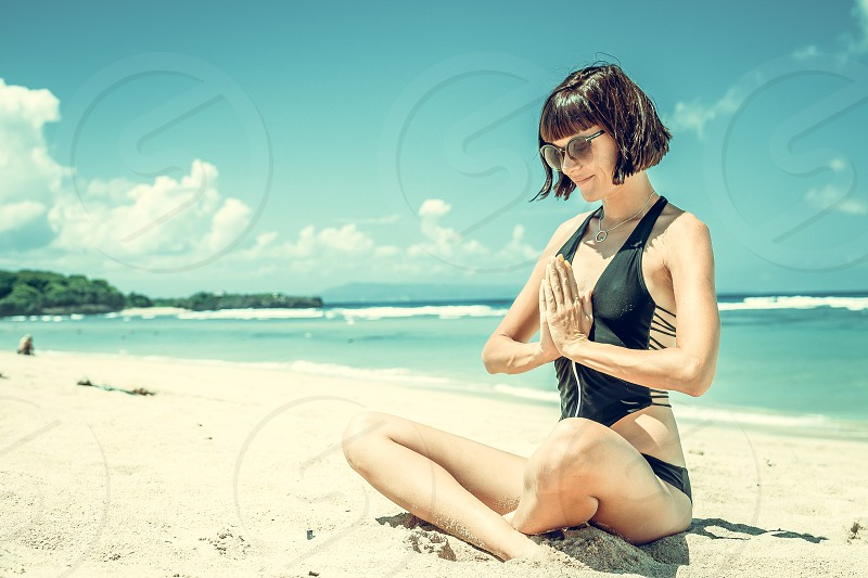 Young healthy attractive woman practicing yoga on the beach Nusa Dua tropical Bali island Indonesia. photo