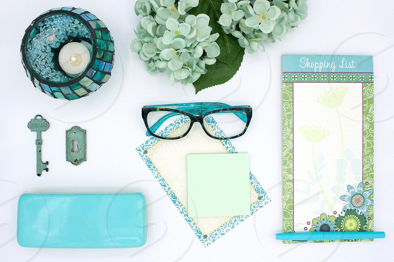 Teal and turquoise flat lay items on white desk  photo