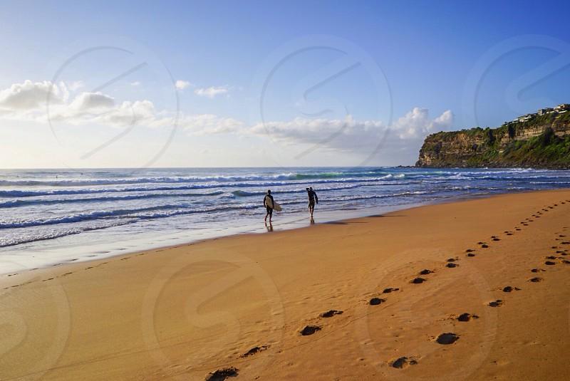 Surfers surf beach surfboard waves footprints sand sea sky photo
