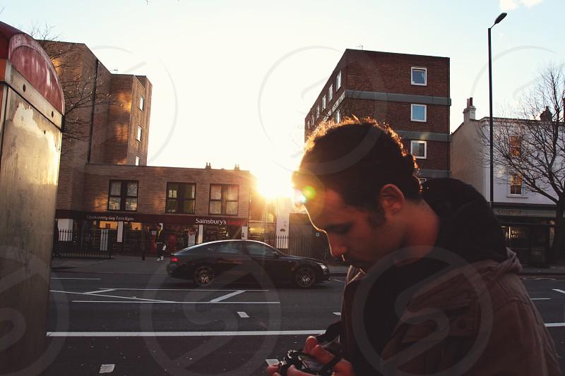 man holding camera near black sedan  photo