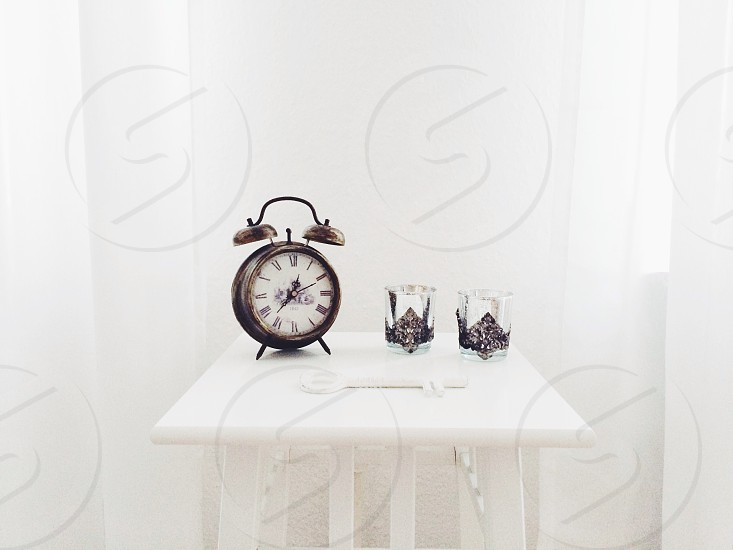 black and white faced analog alarm clock photo