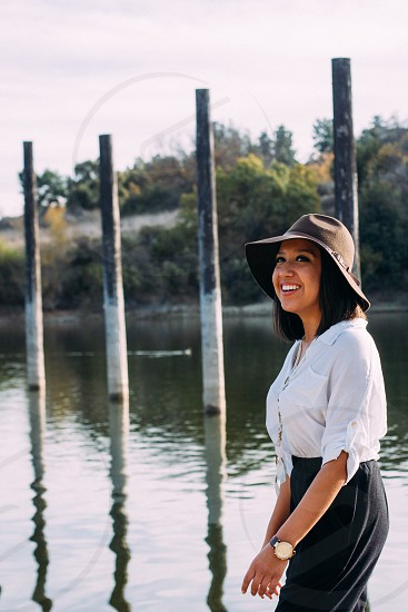 woman wearing brown hat and white button down blouse near lake photo