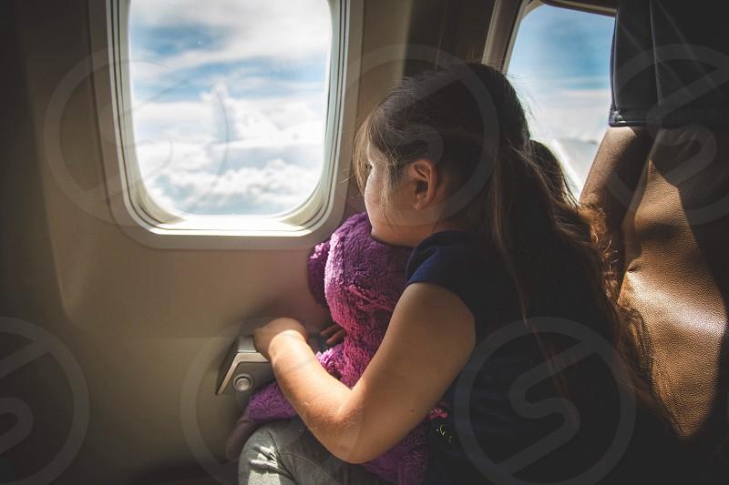 kid on black shirt with purple plush toy on near airplaine window photo