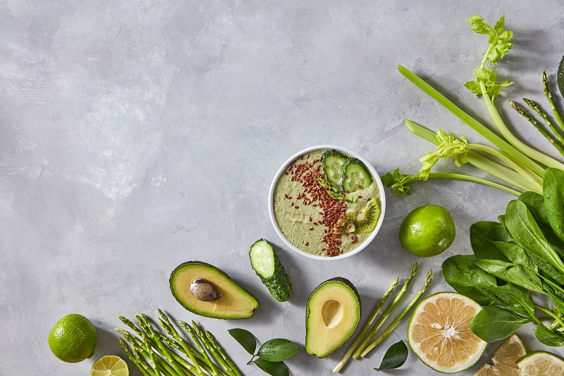 Halves of avocado lime cucumber asparagus spinach and a plate with freshly prepared smoothies with flax seeds on a gray concrete background with a copy of the space. Frame food. Top view photo
