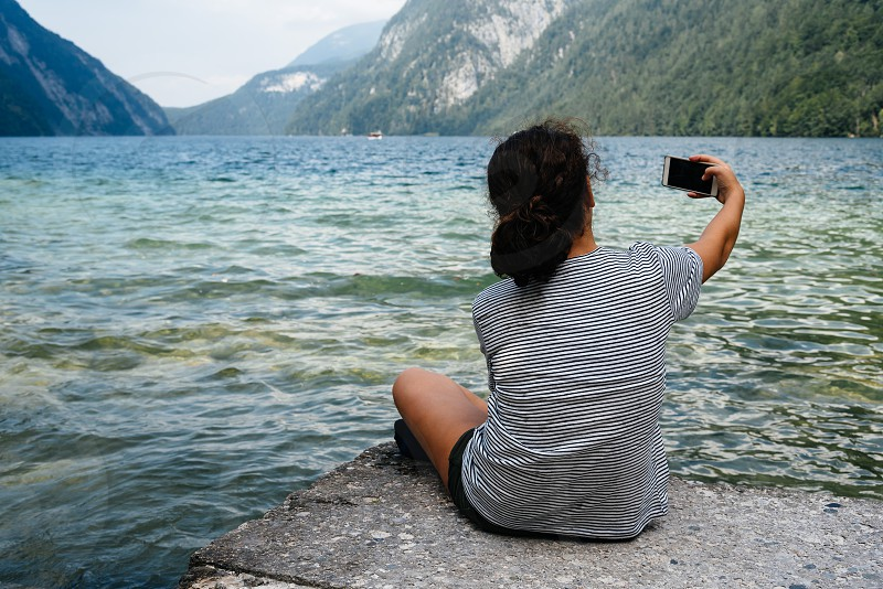 Beautiful girl sitting by the lake taking a selfie. Space for copy photo