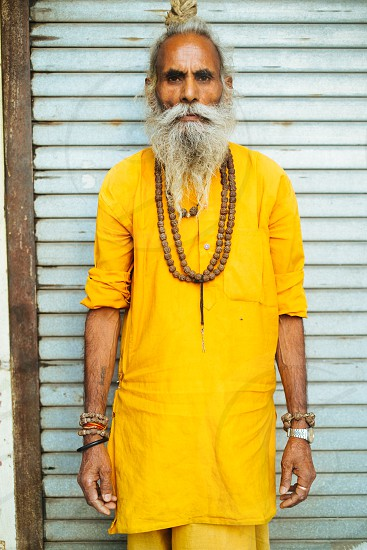 Indian man with grey-haired beard and mustaches stand in front of the wall in vivid yellow clothes. photo