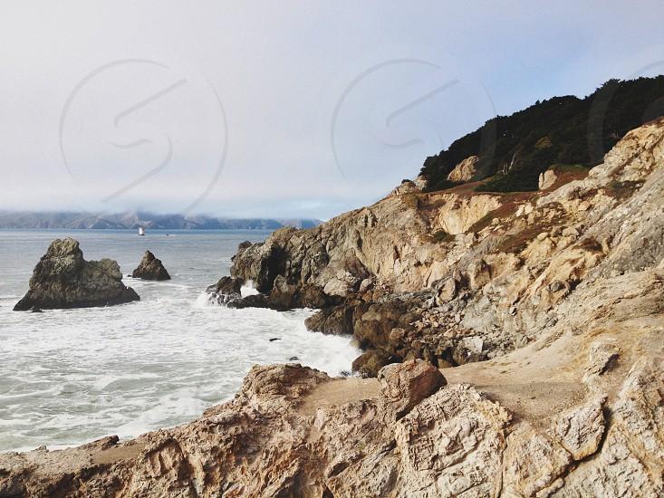 white waves along brown mountain photo
