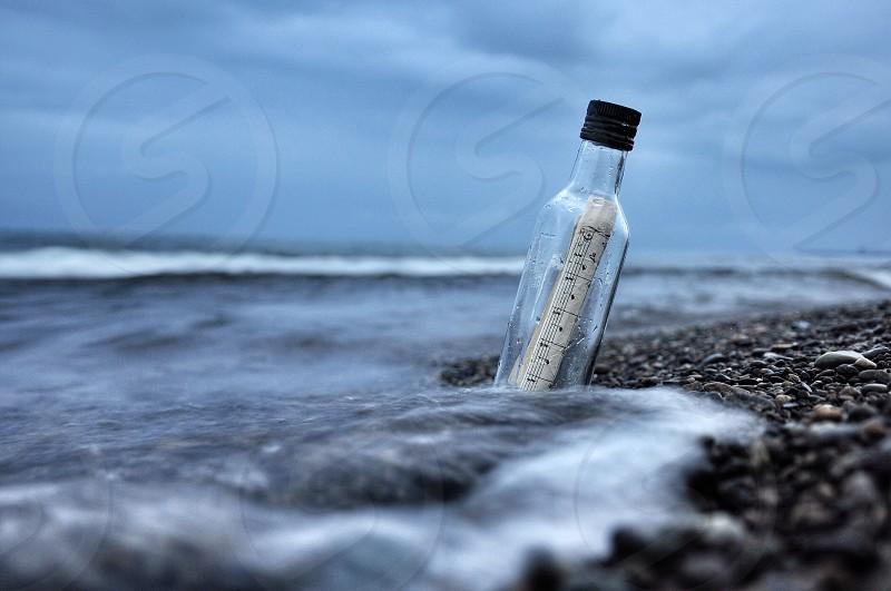 message in a bottle near sea shore photo