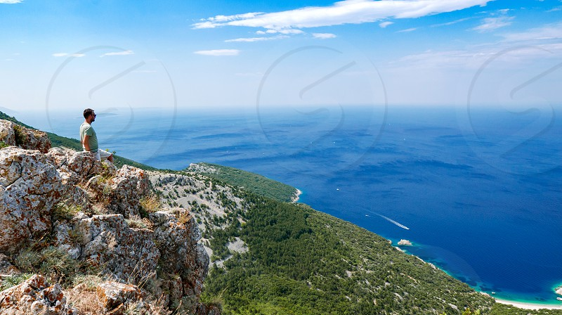 Man standing on a cliff high above the sea. photo
