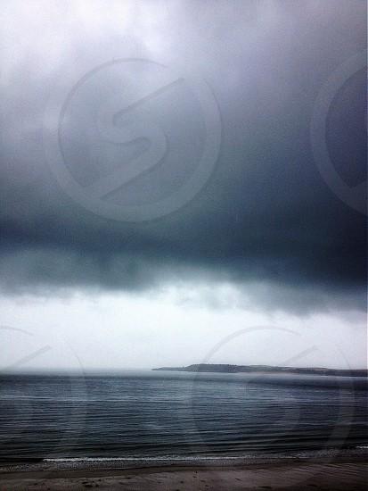 dark clouds over the calm sea photo