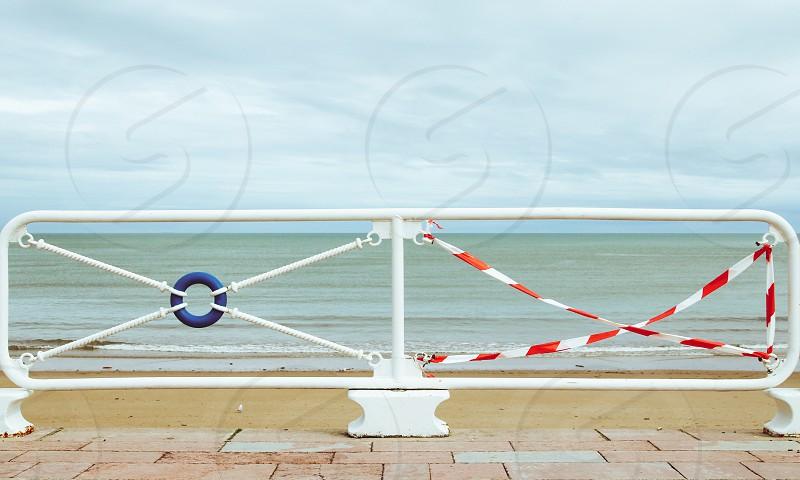 Broken railing against the beach photo