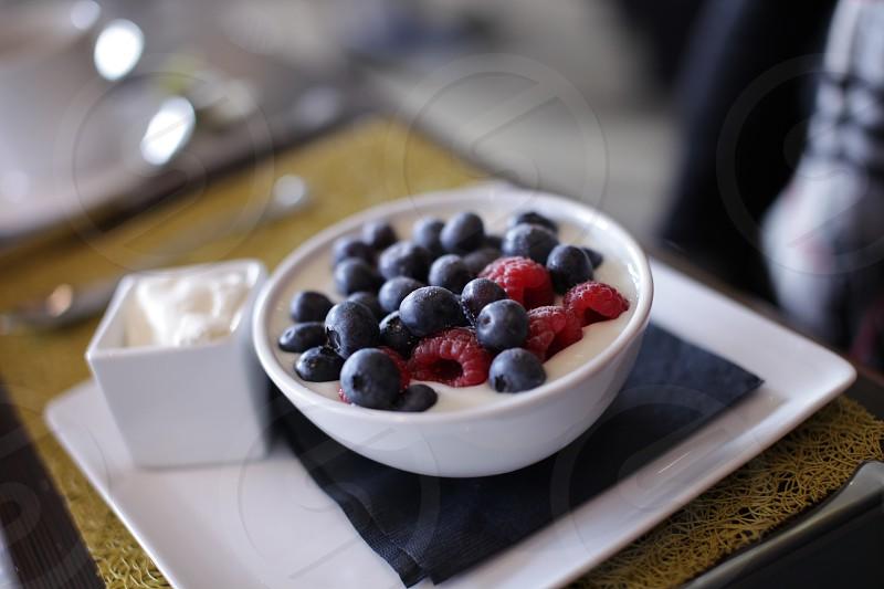 red raspberries and black berries on white ceramic bowl photo