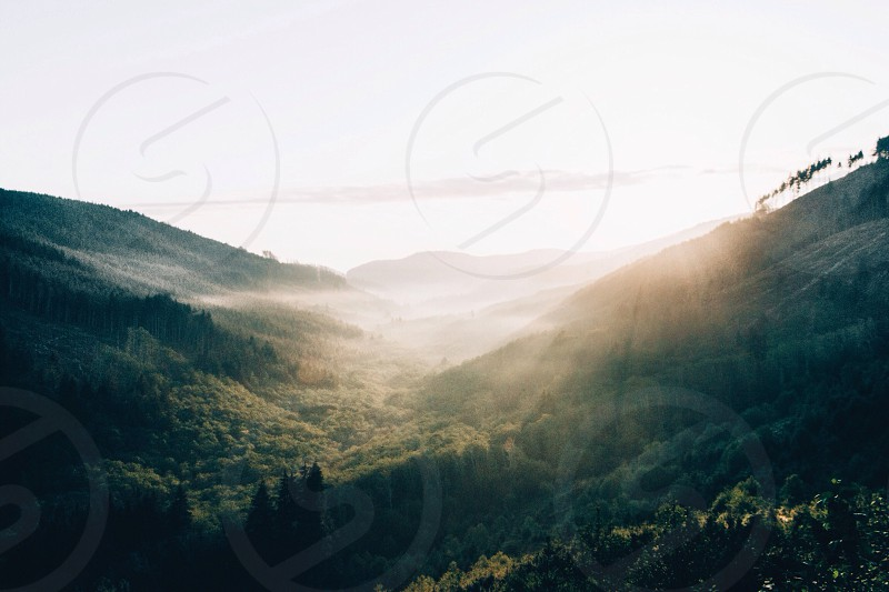 high angle view of the sunrise through the green mountains photo