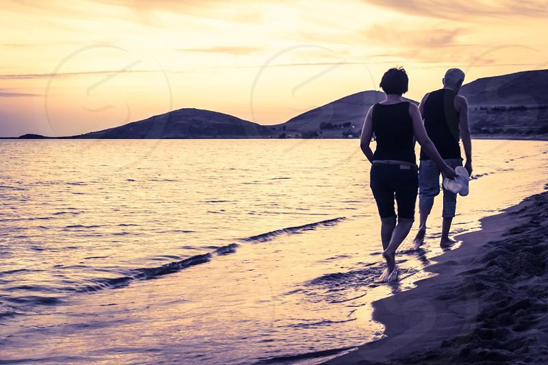Senior Couple On Vacation Walking On The Beach At Sunset photo