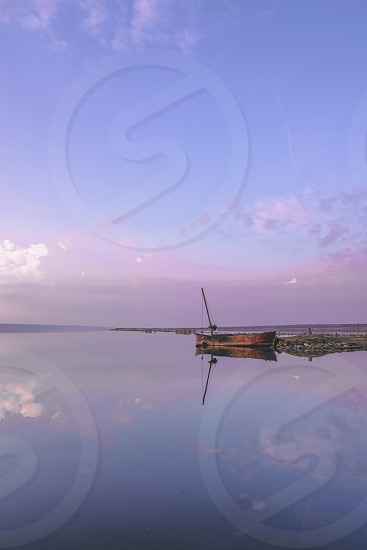 Panoramic view of the clouds above the water in a pink and purple sunset photo
