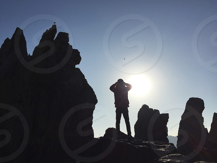 man standing on rock near cliffs under white clouds and blue sky during daytime photo
