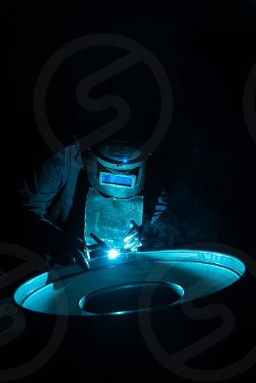 Skilled welder welding a circular metal part under dramatic lighting. photo