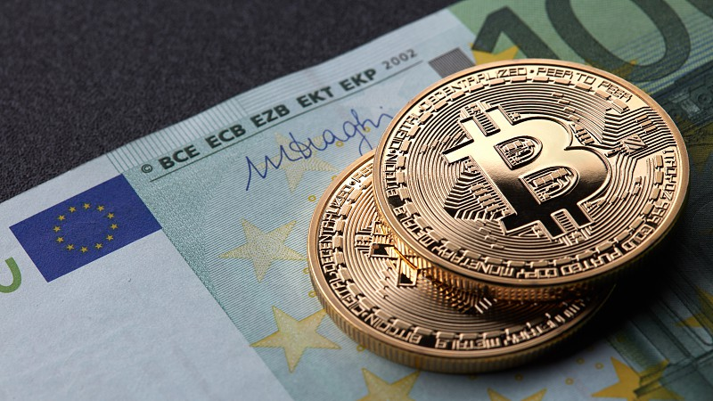 Two gold coins bitcoin stack on paper euro bill. Investing in crypto currency. Exchange bitcoin cash for a dollar. photo