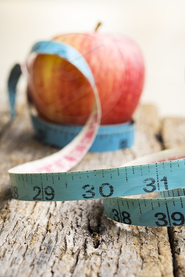 Close-up of measurement tape with red apple in the background on old wooden table photo