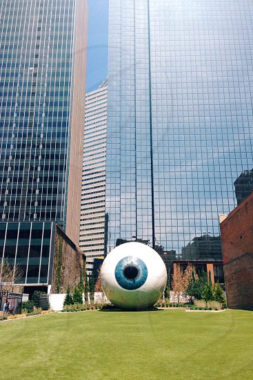 white and blue eyeball statue in front of high rise building photo
