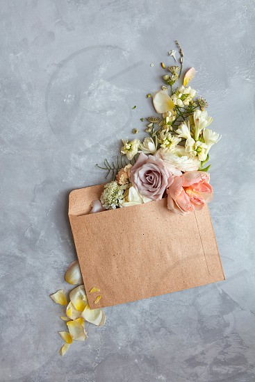 The message in the letter. Beautiful bouquet of flowers in an envelope on a stone gray background as a concept for the holiday Flat lay. photo