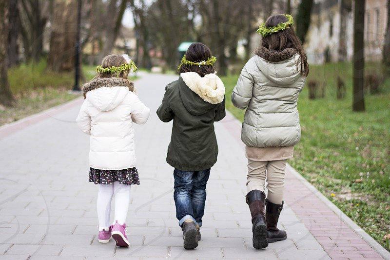 Three siblings walking in the park eating popcorn. Two sisters and one brother. photo