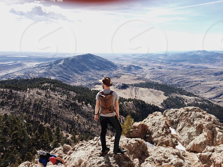 man with brown backpack on top of mountain during daytime photo
