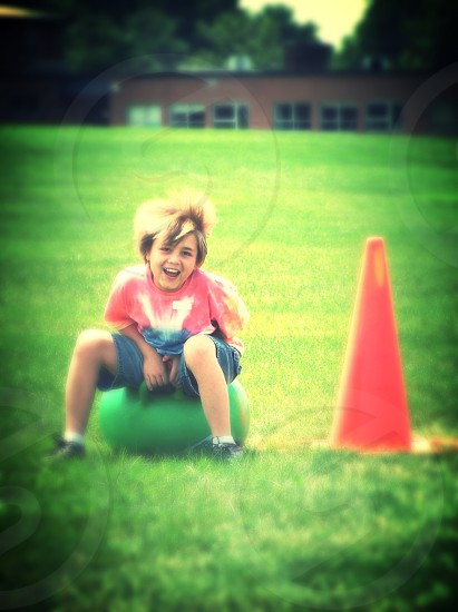 a boy sitting in a rubber ball next to a orange traffic cone photo