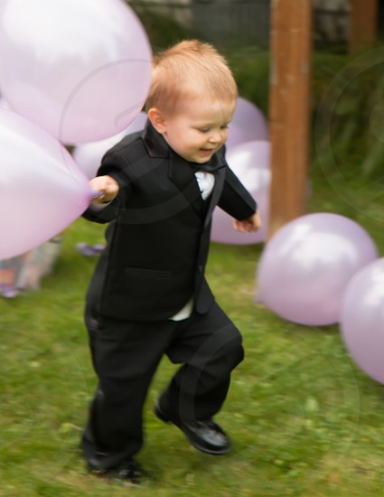 boy in tuxedo playing with balloons photo