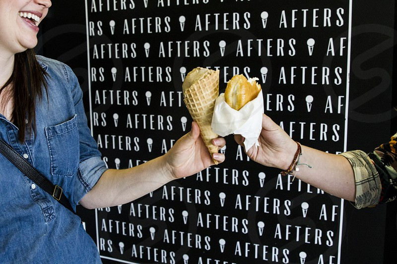 woman in blue denim polo holding ice cream cone cheering to a person holding burger sandwich at afters photo