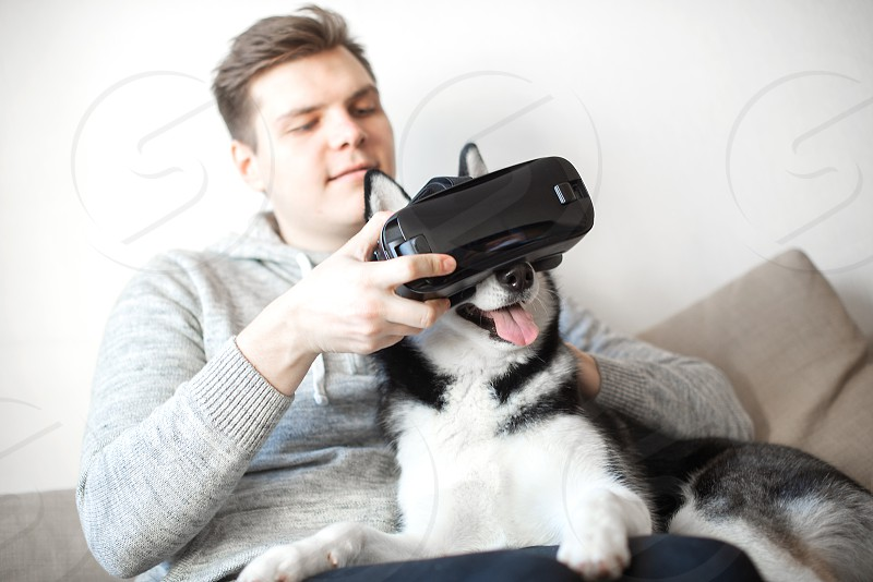 Young man and cute husky dog using glasses of virtual reality photo