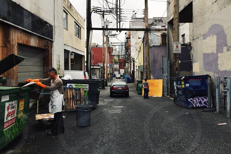 Man Wearing White Apron Standing in Front of Green Garbage Can photo