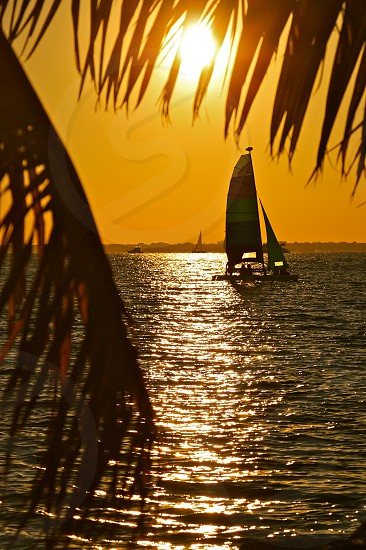 yellow red green and blue sailboat on body of water under orange sunset photo