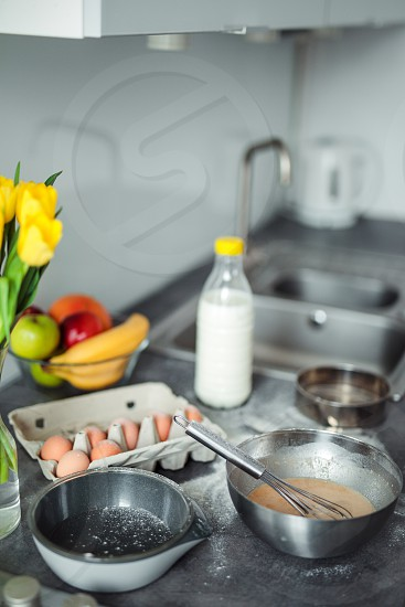 Up down shot of pancakes in the kitchen home with flowers eggs fruits on the table. photo