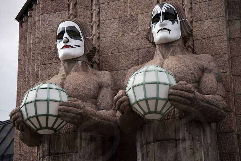 HELSINKI FINLAND - 1 May 2017: Iconic stone men statues by the side of the entrance to the Helsinki Central Railway Station decorated as wearing heavy rock band Kiss masks during First of May celebrations in Helsinki Finland.  photo