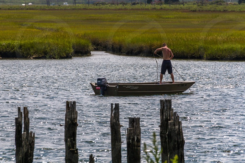 Pulling up anchor on the driftway. Lone boater on the water in coastal marshes. boat water ocean marsh photo