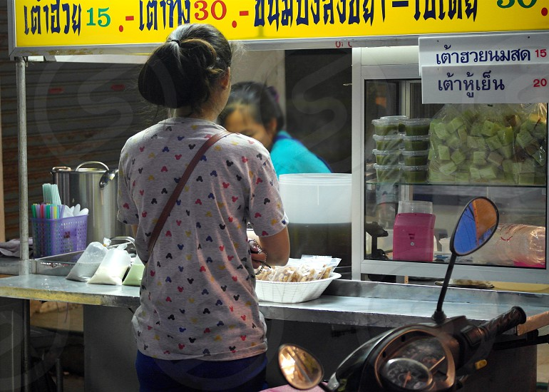 long haired man wearing white blue and red sleeved shit with brown sling bag standing on front of food stall photo