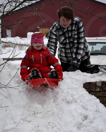 Boy pushing girl in red on a snow sled photo
