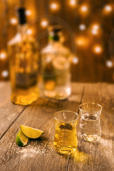 Two small shot glasses of tequila on a wooden background photo