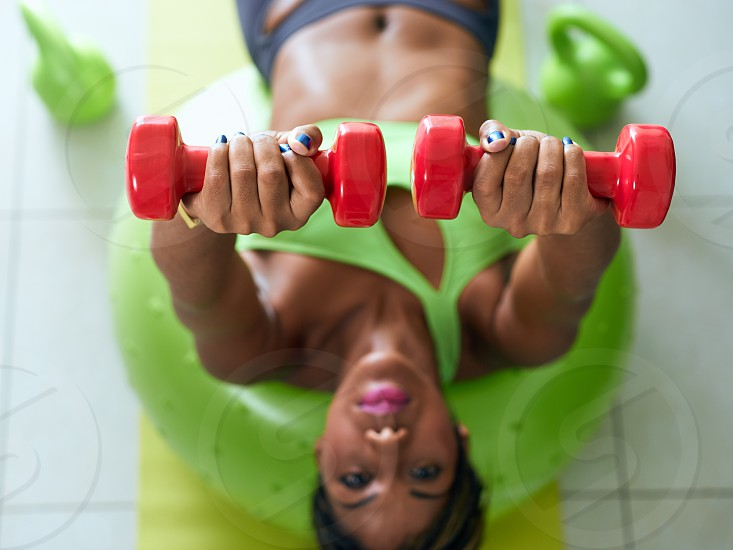 lifting woman home workout training pectoral pectorals 20s active african alternate american athlete ball beautiful black body bodycare clothing domestic dumbbell exercise exercising female fitness focus on foreground high angle view girl house indoor laying lifestyle lift looking at camera muscular one people person raise raising selective focus sport sports sportswear swiss ball waist up weight wellness working out young photo
