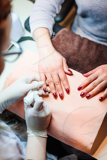 Beautician in a beauty salon doing a hybrid manicure. Painting and styling nails. Woman getting professional nails treatment. Close up of hands photo